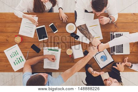 Team bump fists, show connection and alliance, top view of working table. Teambuilding in office, young businessmen and women in casual unite hands for teamwork and cooperation at new project.