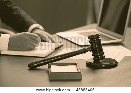 Hands of  lawyer and judge gavel on table. Retro style