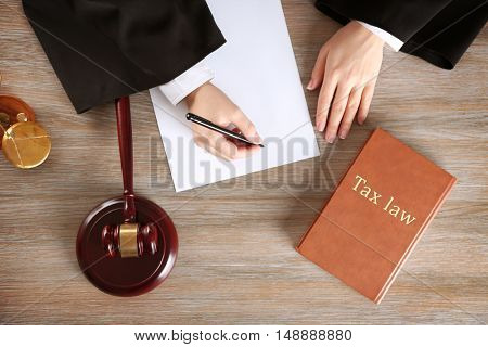 Judge writing on paper with gavel on wooden table, top view. Tax law concept