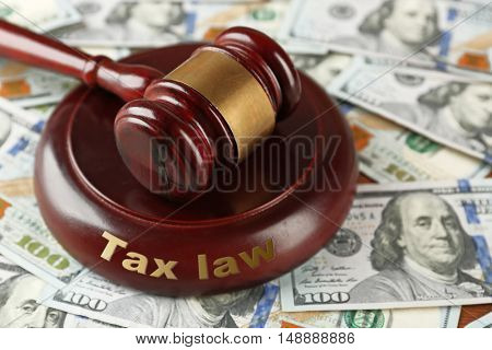 Law gavel on dollars background, closeup. Tax law concept