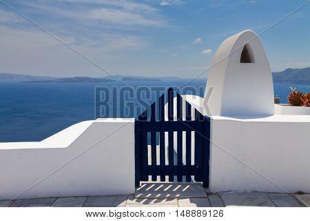 dark blue gates against volcano caldera and Aegan sea, beautiful details of Santorini island, Greece