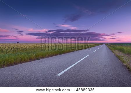 Driving on an empty asphalt road through the agricultural fields at idyllic sunset. Titel hill Serbia.