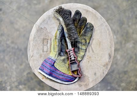 Dirty worker's glove holding a wire brush on a wooden plank in a workshop