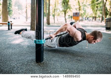 Healthy handsome active man with fit muscular body doing workout exercises.
