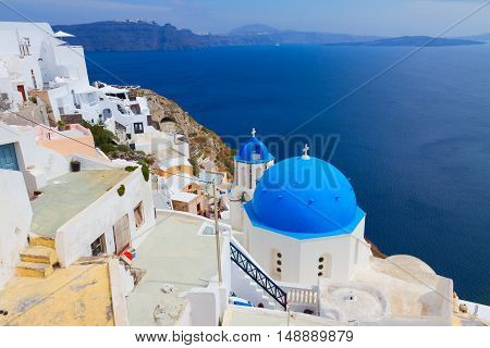 view of caldera with blue church dome and belltower, Oia, Santorini