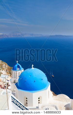 traditional blue dome of church with bellfry against blue sea, Oia, Santorini