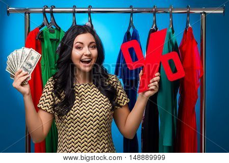 Happy Woman Holding Percent Sign And Hundred-Dollar Bills At The Clothing Rack With Dresses On Blue Background