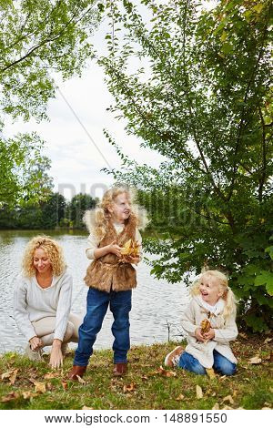 Two kids and woman in autumn collecting leaves at park near a lake