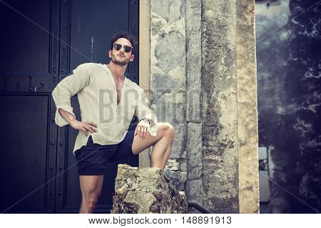 Handsome man leaning against old wall and green door in a summer day