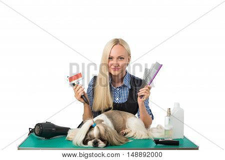 Beautiful smiling woman groomer with combs and cute shih-tzu dog - isolated on white