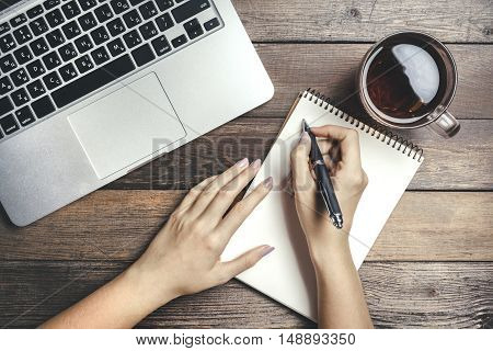 Female Hands Holding A Pan, Wrote In A Notebook  On Vintage Wooden Table. Mock-up With Laptop, Cup And Pan On Notebook