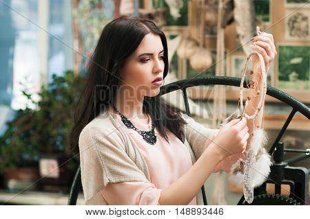 Beautiful woman looking at new dream catcher. Female artisan finishing her decorative creation at workshop. Art, handicraft, hobby, creativity concept