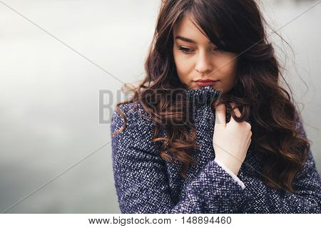 Young woman warming herself in autumn. Cold fall day with copy space