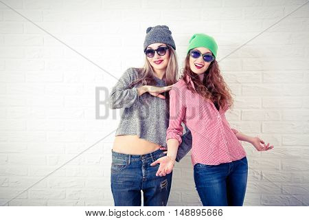Two Happy Smiling Hipster Girls Posing at White Brick Wall Background. Trendy Casual Fashion Outfit in Autumn or Spring. Teenage Friendship and Lifestyle Concept. Toned Photo with Copy Space.