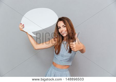Happy young woman holding blank speech bubble and showing thumbs up over grey background