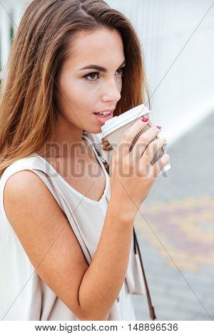 Beautiful brunette woman drinking take away coffee while walking on the street