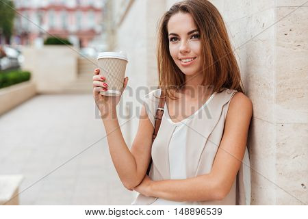 Happy woman holding take away coffee and looking at camera while standing on the street