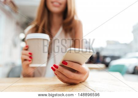 Cropped image of a young woman typing message on smartphone and drinking cup of coffee in cafe