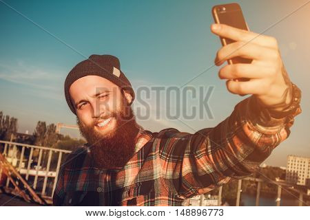 Handsome Bearded Man In Red Shirt Makes Selfie On His Phone On A Bridge Near The River