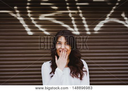 Beautiful brunette woman surprised over street wall with copy space above head. Cute girl with big eyes smiling over brown background
