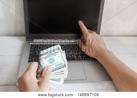 Laptop blank screen and batch of hundred dollar bills. Male hand point at computer monitor with american dollars in hand. Income through internet, finance, earning concept. Mockup
