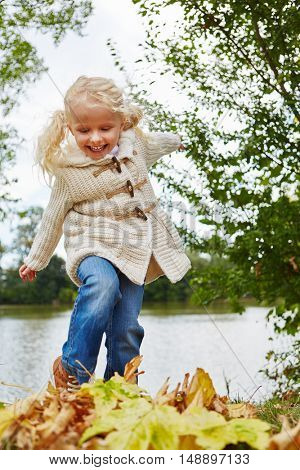 Blond girl playing with leaves in autumn at the park