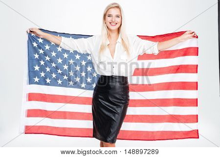 Cheerful young businesswoman holding flag of United states over white background