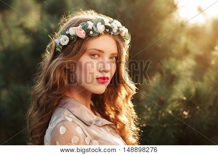 Semi profile portrait of beautiful girl in wreath, free space. Attractive young smiling woman in forest, blurred pine-tree background, sunset light.