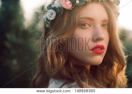 Young casual bride in wreath close-up portrait, free space. Beautiful fashion woman with perfect makeup posing outdoor in sunset light, blurred pine forest background