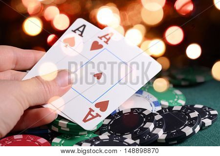 Casino chips and pair of aces in a croupier's hand against bright bokeh lights. Poker game theme backdrop.
