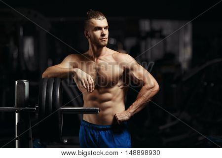 Attractive muscular bodybuilder guy prepare to do exercises with barbell in a gym. Guy bodybuilder tired in gym. Young Man Bodybuilder Resting In Gym After Exercising
