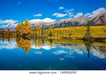 The concept of recreational tourism. Bright shining autumn day in Canmore, near Banff National Park. Scenic cumulus clouds are reflected in the lake