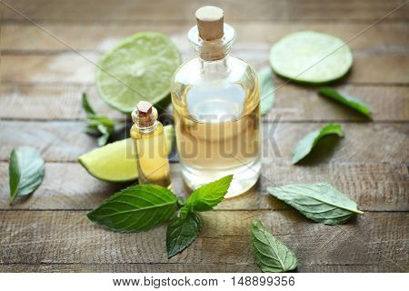 Bottles with mint oil, lime and fresh leaves on wooden background