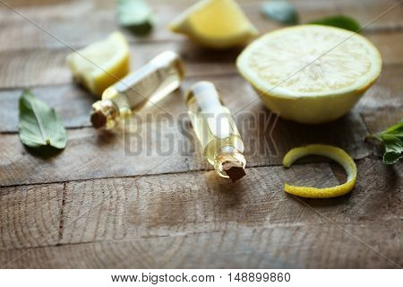 Bottles with mint oil, lemon and fresh leaves on wooden background