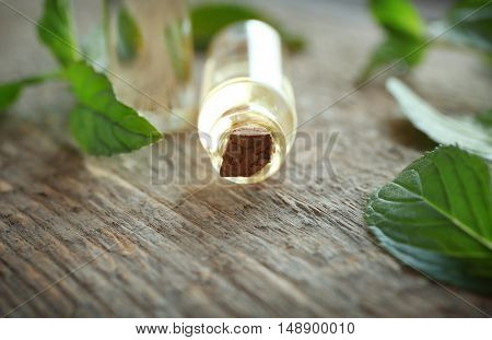 Bottle with mint oil and fresh leaves on wooden background