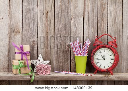 Christmas gift boxes, alarm clock and food decor in front of wooden wall. View with copy space