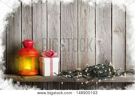 Christmas candle lantern, xmas lights and gift box in front of wooden wall. View with copy space for your text