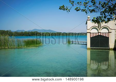 Old beautiful boathouse reflected in shallow light blue water of a pristine lake surrounded by wooded hills on a sunny day