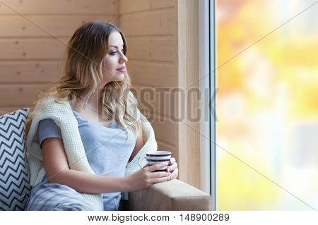 Young beautiful blonde woman with cup of coffee sitting home by the window. Backyard reflection on the glass. Lazy day off concept