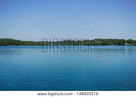 Rowing lane marked by orange and white buoys on a peaceful lake surrounded by hills under a clear blue sky