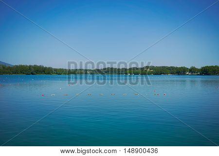 Lines of buoys marking rowing lanes on a peaceful greenish blue lake under a quiet sunny sky