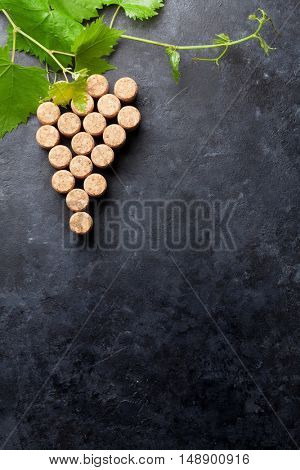 Wine corks grape shape and vine on stone table. Top view with copy space for your text