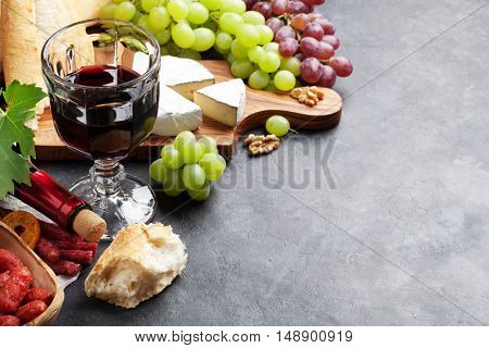 Red wine, grape, cheese, bread and sausages over stone table. View with copy space