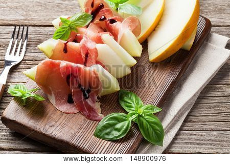 Fresh melon with prosciutto and basil. Antipasti. On wooden table