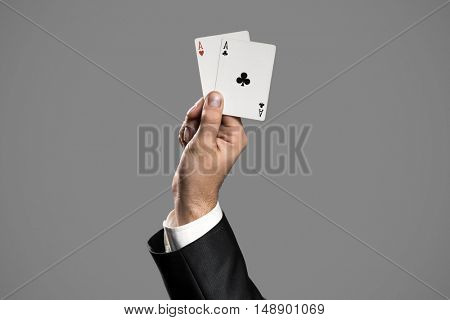 A Businessman Holding An Aces On Gray Background. Ace In The Hole.