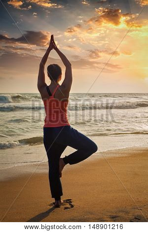 Yoga outdoors - sporty fit woman doing Hatha yoga asana Vrikshasana tre pose on tropical beach on sunset