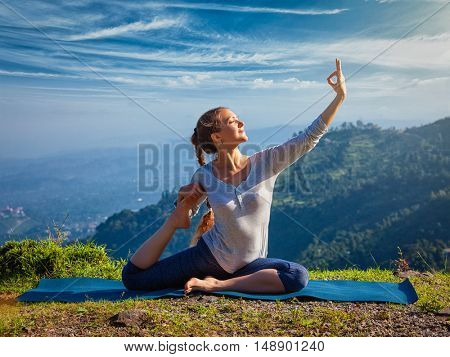 Yoga outdoors - young sporty fit woman doing stretching yoga asana Eka pada rajakapotasana - one-legged king pigeon pose in Himalayas mountains, India
