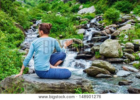 Yoga exercise outdoors -  woman doing Ashtanga Vinyasa Yoga asana Marichyasana D seated spinal twist pose at waterfall in mountains
