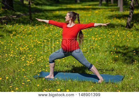 Pregnancy yoga exercise - pregnant woman doing yoga asana Virabhadrasana 2 warrior pose outdoors on grass in summer