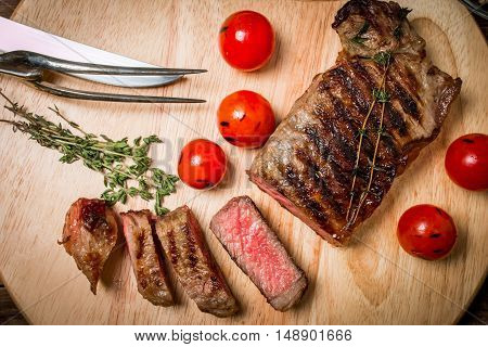 Sliced medium rare grilled Beef steak Ribeye with cherry tomatoes on cutting board on wooden background,  top view